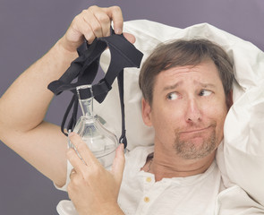 Man examines a CPAP mask