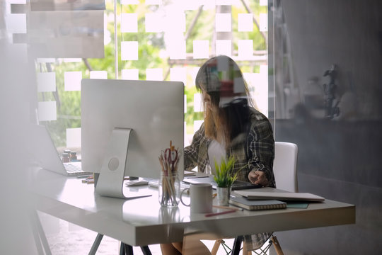 Young asian female designer using graphics tablet while working with computer at studio or office.
