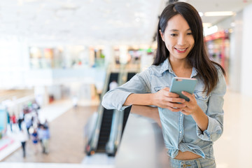 Woman looking at mobile phone inside shopping mall