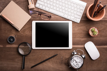 White Tablet With Blank Screen On Wooden Desk With Stationery Objects , Top View