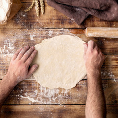 Fototapete - Man prepares the dough for cooking pizza on wooden table