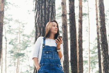 Young woman in jeans overalls with smartphone standing in woodland