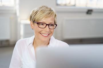 lächelnde mitarbeiterin schaut auf ihren pc