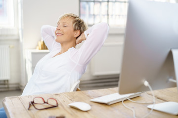 frau am arbeitsplatz lehnt sich entspannt zurück und schließt die augen