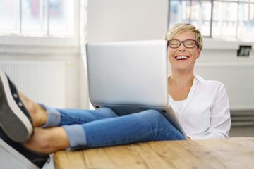 frau arbeitet zuhause am laptop und lacht