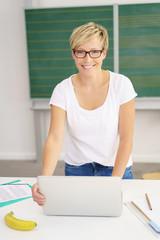 moderne, lächelnde lehrerin mit laptop in der klasse