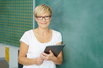 lächelnde lehrerin mit tablet vor der tafel