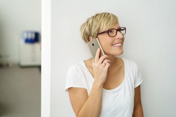 frau telefoniert im büro und schaut lächelnd nach oben