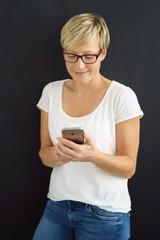 moderne frau mit kurzen, blonden haaren schaut auf ihr handy