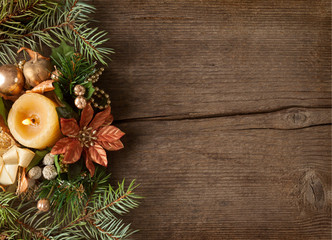 Fir branch with Christmas decorations  and candle on the background of old wooden plank.