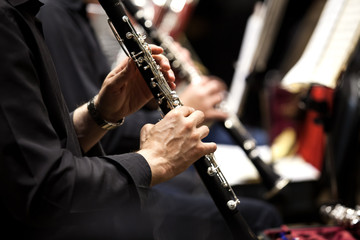 Hands of man playing the clarinet in the orchestra