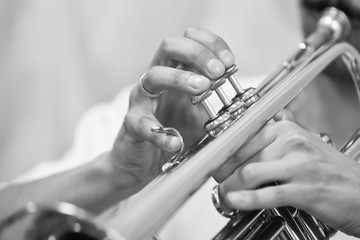 Hands of a musician playing on a trumpet closeup in black and white tones