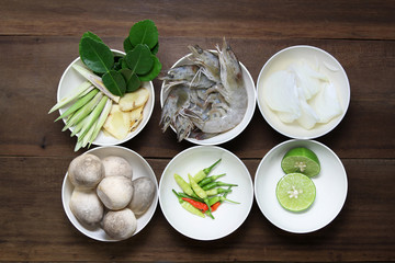 Ingredient of tom yum ( Lemongrass, Galangal, kaffir lime leaf,shrimp, onion, Paddy straw mushroom ,chili and lime) in white bowl on wooden background, thai food, prepare food.