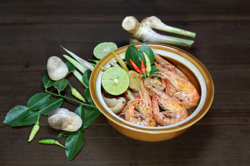 Tom Yum Kung Shrimp clear soup  is decorated with lime, red pepper, lemongrass, galangal, kaffir lime leaf, chilli paste and mushroom on wooden background, Hot and spicy food, Thai food.