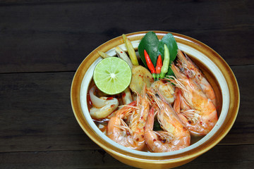 Tom Yum Kung Shrimp clear soup on wooden background, Thai food, cuisine.