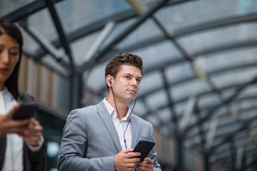 Businessman listening to podcast waiting for train at station