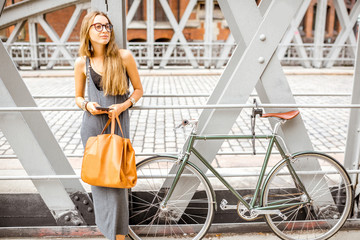 Young stylish business woman standing outdoors with retro bicycle on the iron bridge