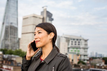 Businesswoman using smartphone with London city skyline