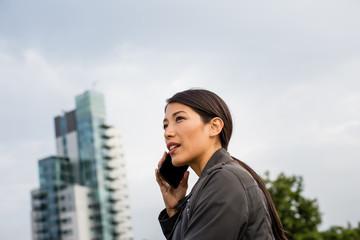 Businesswoman using smartphone with skyscraper in background