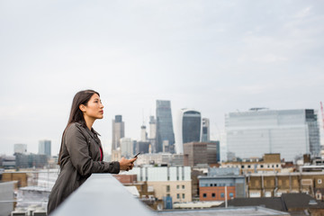 Businesswoman looking out at London city skyline