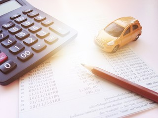Business, finance, saving money, banking or car loan concept : Miniature car model, calculator and saving account book or financial statement on office desk table