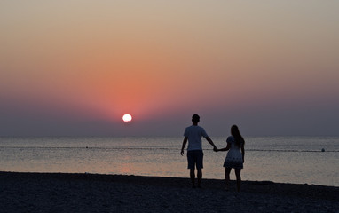 Junges Paar spaziert dem Sonnenaufgang entgegen