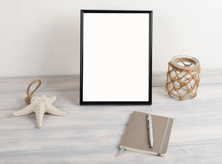 Picture frame next to decorative objects on wooden table. Decor.