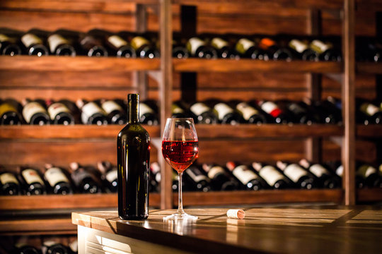 Bottle and glass filled with red wine placed on a wooden table. Wine vault location.