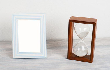Photo frames next to hourglass on wooden table. Decor.