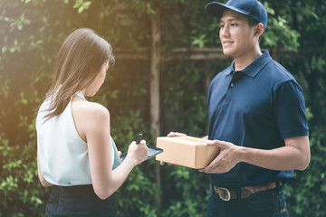 Handsome young asian delivery man smiling and holding a cardboard box while waiting beautiful young asian woman putting signature in smart tablet for confirm receive.
