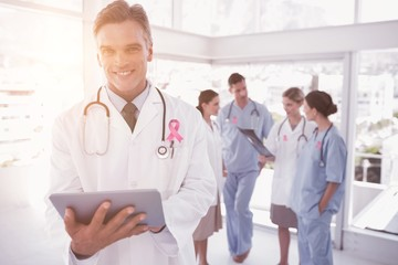 Composite image of smiling doctor holding digital tablet