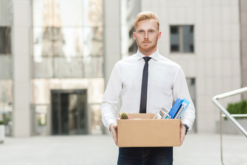 Unhappy bearded business man going out with cardboard, looking at camera and feeling looser.