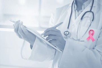 Composite image of mid section of a female doctor writing