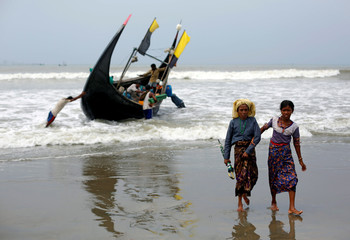 Rohingya refugees walk to the shore after crossing the Bangladesh-Myanmar border by boat through the Bay of Bengal in Teknaf