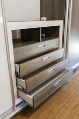 Fototapeta open wooden drawers in the closet obraz