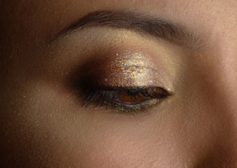 Close-up portrait of young woman with golden makeup.