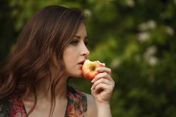 A young beautiful woman holding a ripe apple on a green background