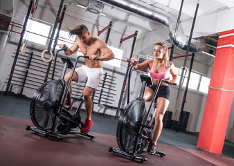 Fit couple on cycling machines doing exercise together at gym