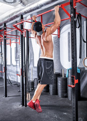 Bodybuilder showing muscular back during pull ups exercise at gym