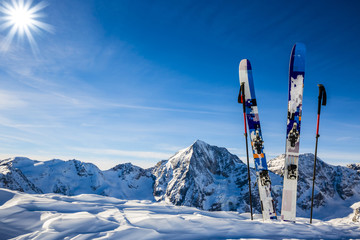 Fototapete - Ski in winter season, mountains and ski touring backcountry equipments on the top of snowy mountains in sunny day. South Tirol, Solda in Italy.
