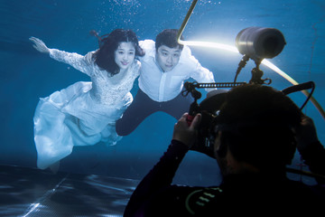 The Wider Image: Flights, camera, action: Chinese couples strike a pose