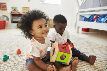 Baby Boy And Girl Playing With Toys In Playroom Together