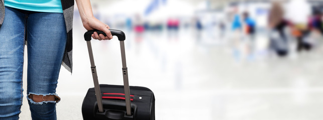 woman walking with suitcase at airport terminal. copy space