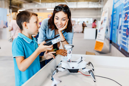 Mother and son are studying robotics and modern electronics at an educational exhibition