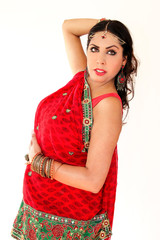 Woman dancing Indian dance in national dress. A handsome beautiful girl portrait in red Hindu Saree, horn for the Indian dance movement. Indian dancer in traditional clothing. Bollywood dance. Beauty.
