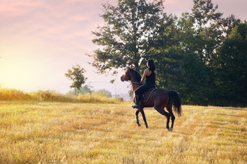 Woman riding a horse in sunset