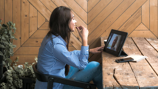 Beautiful cute Caucasian young female with long black hair in rustic cafe, having a video call with a friend.