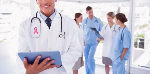 Composite image of smiling doctor holding digital tablet