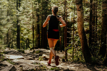 Fototapete - girl runner running trail stone in forest in knee pads
