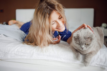 Portrait of a beautiful woman in pajamas at home, lying in bed. Pat the cat